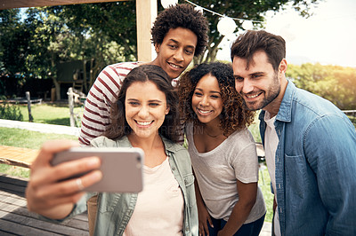 Buy stock photo Shot of a group of friends taking selfies together outdoors