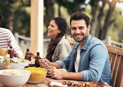 Buy stock photo Portrait of a young man having a meal with friends outdoors