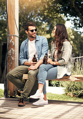 Buy stock photo Shot of a young couple drinking beer together outdoors