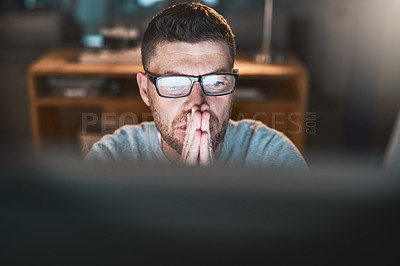 Buy stock photo Shot of a mature businessman looking worried while working late on a computer in an office