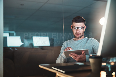 Buy stock photo Shot of a mature businessman working late on a digital tablet in an office