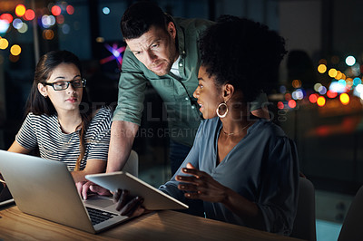 Buy stock photo Shot of a group of designers working late on a digital tablet in an office