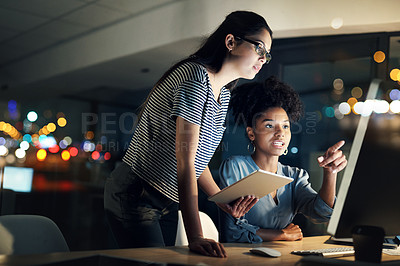 Buy stock photo Shot of two designers working late on a computer in an office