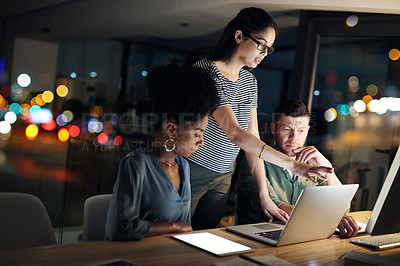 Buy stock photo Shot of a group of designers working late on a laptop in an office