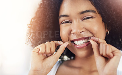 Buy stock photo Cropped shot of a beautiful young woman flossing her teeth