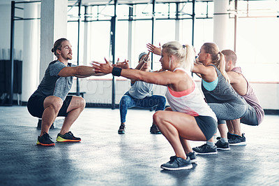 Buy stock photo Shot of a fitness instructor working with a group of people at the gym
