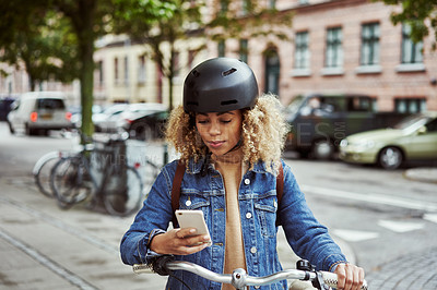Buy stock photo Shot of an attractive young woman using her cellphone while out cycling through the city