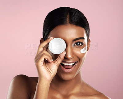 Buy stock photo Studio shot of a beautiful young woman posing with moisturizer on her face against a pink background