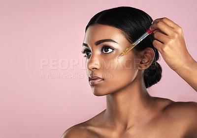 Buy stock photo Studio shot of a beautiful young woman applying essential oil to her face with a dropper posing against a pink background