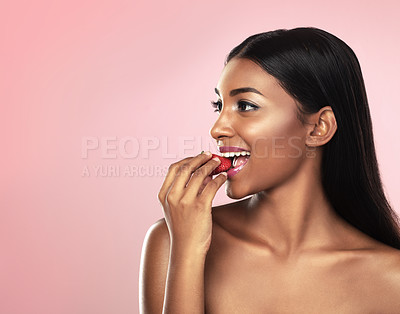 Buy stock photo Studio shot of a beautiful young woman eating a strawberry while posing against a pink background