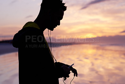 Buy stock photo Silhouette shot of a young man listening to music while standing outdoors