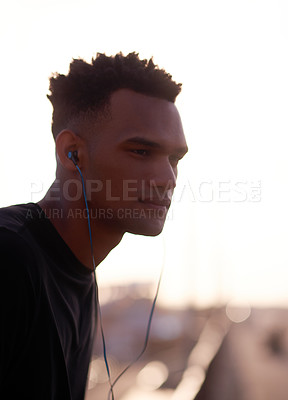 Buy stock photo Cropped shot of a handsome young man listening to music while standing outdoors