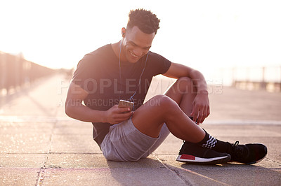 Buy stock photo Shot of a handsome young man siting outside while listening to music