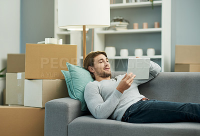 Buy stock photo Cropped shot of a young handsome man using a tablet while chilling on the sofa in his new home