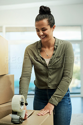 Buy stock photo Cropped shot of a beautiful young woman packing boxes getting ready to move