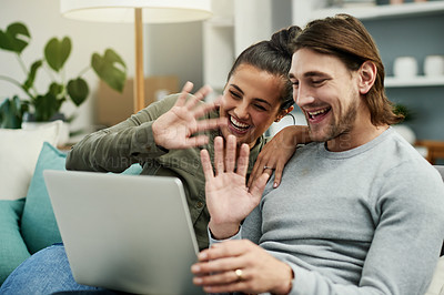Buy stock photo Cropped shot of a young attractive couple video calling using a laptop on the sofa in their new home