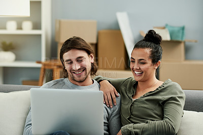 Buy stock photo Cropped shot of a young attractive couple using a laptop together in their new home