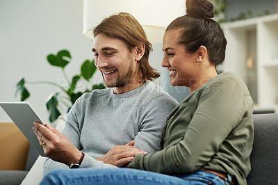 Buy stock photo Cropped shot of a young attractive couple using a tablet together on the sofa in their new home