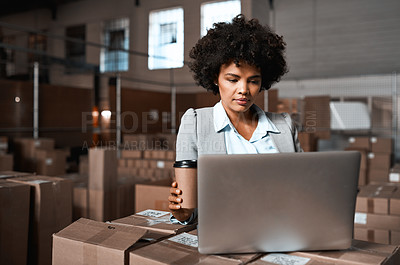 Buy stock photo Shot of a factory manager drinking coffee while working on a laptop in a warehouse