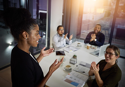Buy stock photo Shot of a young businesswoman being applauded while delivering a presentation to her colleagues in the evening at work
