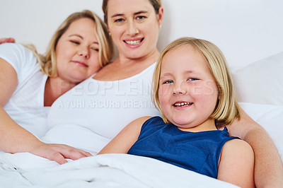 Buy stock photo Shot of an adorable little girl relaxing in bed with her mother's at home
