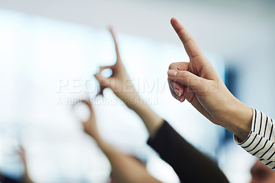 Buy stock photo Cropped shot of a group of unrecognizable people pointing upwards