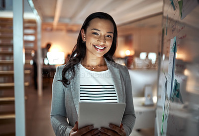 Buy stock photo Cropped portrait of an attractive young businesswoman using a tablet while standing in her office