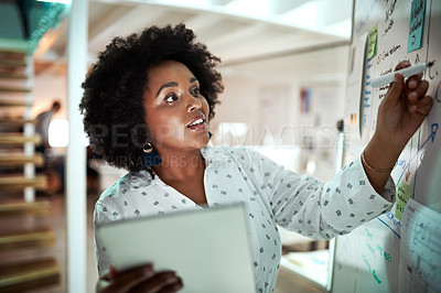Buy stock photo Cropped shot of an attractive young businesswoman using a tablet while working on a glass wipe board in her office