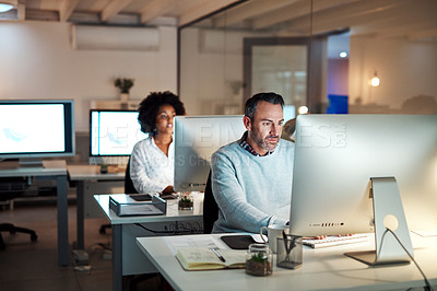 Buy stock photo Cropped shot of a group of businesspeople working at their desks in the office