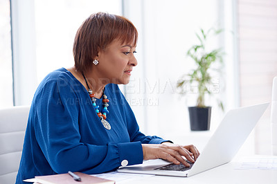 Buy stock photo Shot of a mature businesswoman using a laptop in a modern office