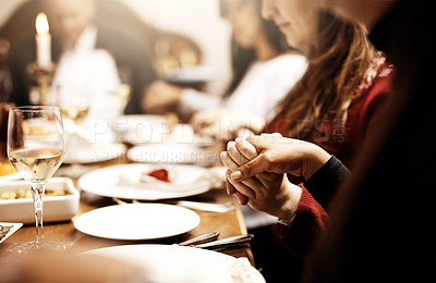 Buy stock photo Cropped shot of unrecognizable people holding hands in prayer before having a Christmas lunch together