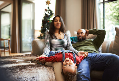 Buy stock photo Cropped shot of a happy young family chilling in their living room on Christmas morning