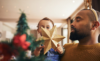Buy stock photo Cropped shot of a handsome young man and his daughter decorating the Christmas tree for the festive season