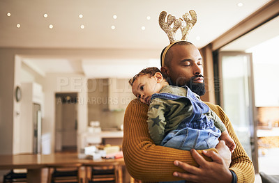 Buy stock photo Cropped shot of a handsome young man carrying his daughter through the living room on Christmas morning