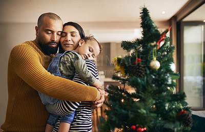 Buy stock photo Cropped shot of a happy young family standing in their living room on Christmas morning