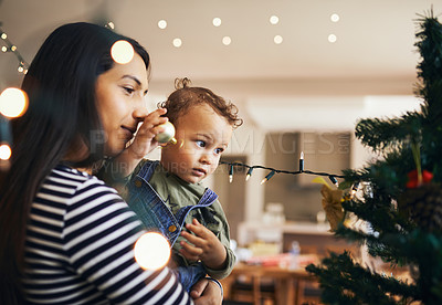 Buy stock photo Cropped shot of an attractive young woman and her daughter decorating the Christmas tree for the festive season