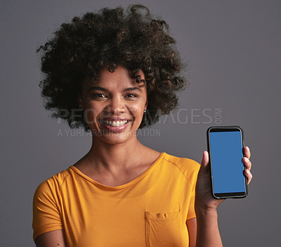 Buy stock photo Shot of a beautiful young woman holding up a cellphone against a grey background