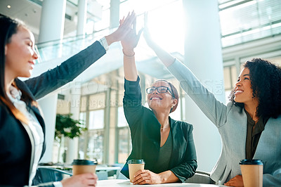 Buy stock photo Cropped shot of young businesswomen giving each other a high five while having a meeting in the convention centre