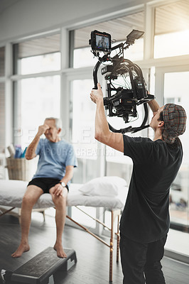 Buy stock photo Behind the scenes shot of a camera operator shooting a scene with a state of the art camera inside of a studio during the day