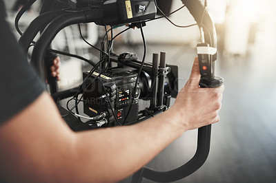 Buy stock photo Behind the scenes over the shoulder shot of an unrecognizable person operating a state of the art video camera inside of a studio