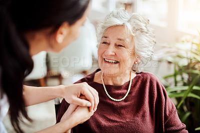 Buy stock photo Shot of a young nurse holding an elderly woman's hands in a retirement home