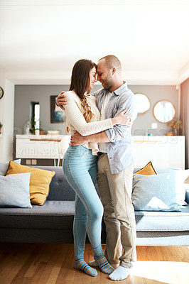 Buy stock photo Shot of a young couple being affectionate in the living room at home