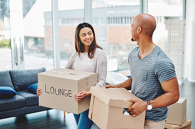 Buy stock photo Shot of a young couple carrying boxes while moving house