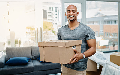 Buy stock photo Portrait of a young man holding a box while moving house