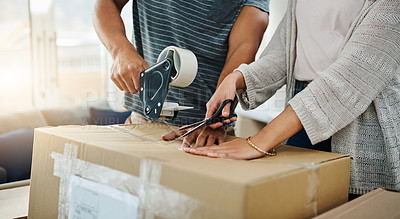 Buy stock photo Closeup shot of an unrecognizable couple sealing a box with tape while moving house