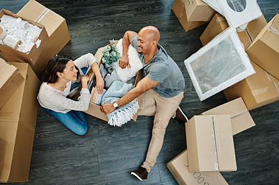 Buy stock photo Shot of a young couple sorting boxes while moving house