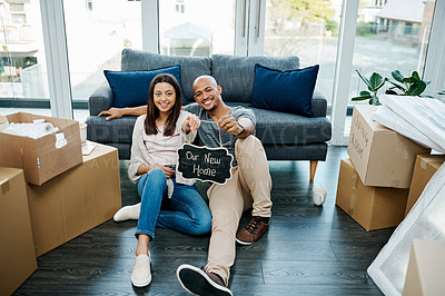 Buy stock photo Portrait of a young couple holding a chalkboard in their new house