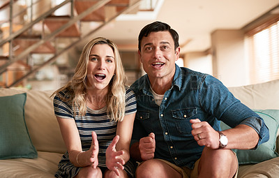 Buy stock photo Cropped shot of a middle-aged couple getting excited while watching something at home