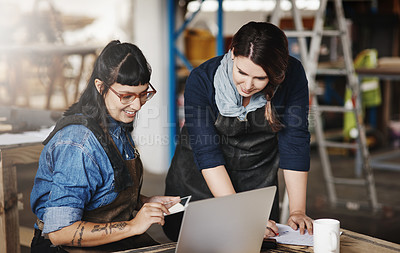 Buy stock photo Cropped shot of two attractive young creative female artisans working on a laptop in their workshop