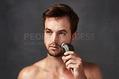 Buy stock photo Cropped portrait of a handsome young man using an electric shaver